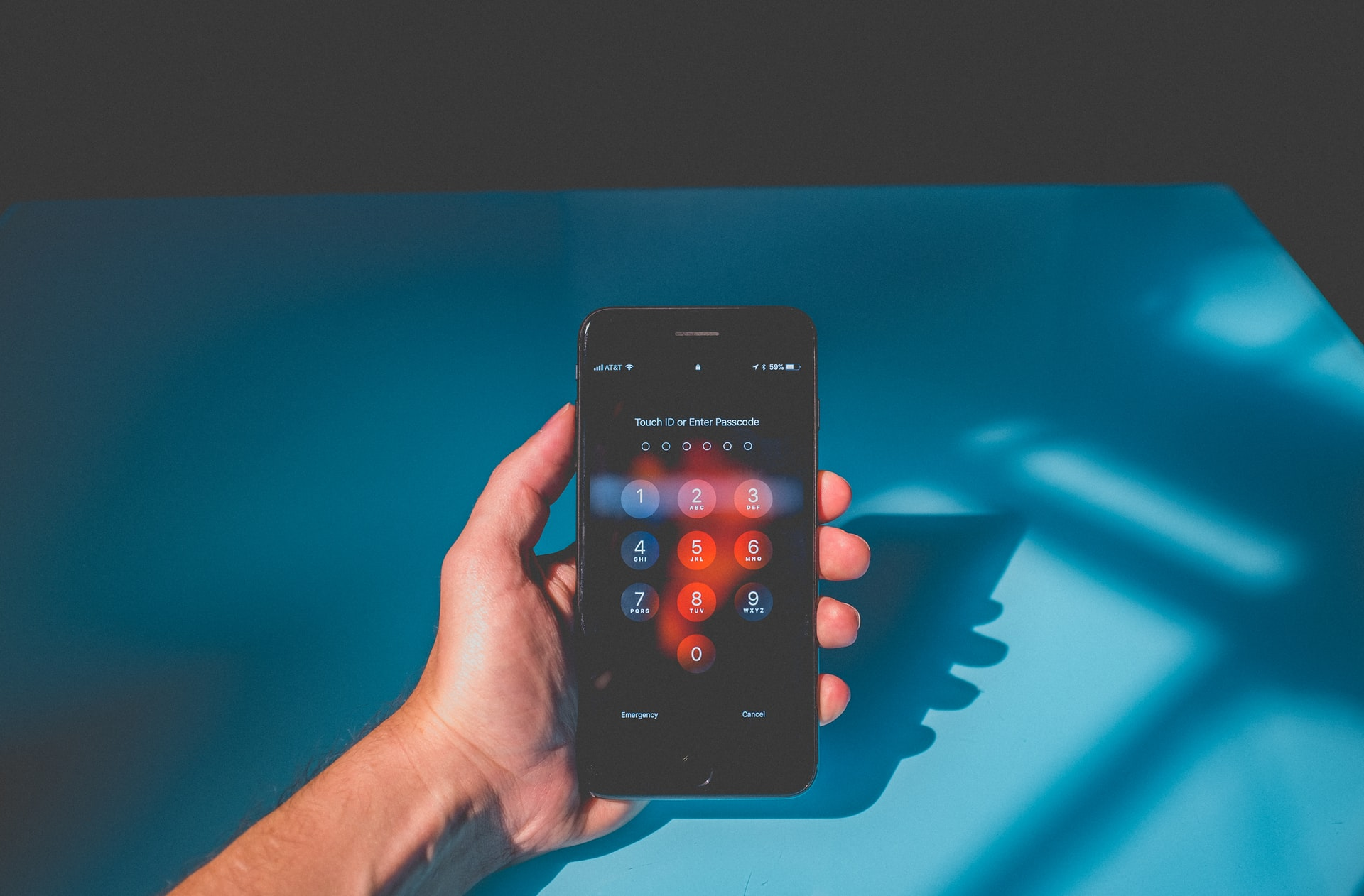 Must-have modern workplace tools to secure your organisation from data loss - hand holding a mobile phone with the passcode screen open